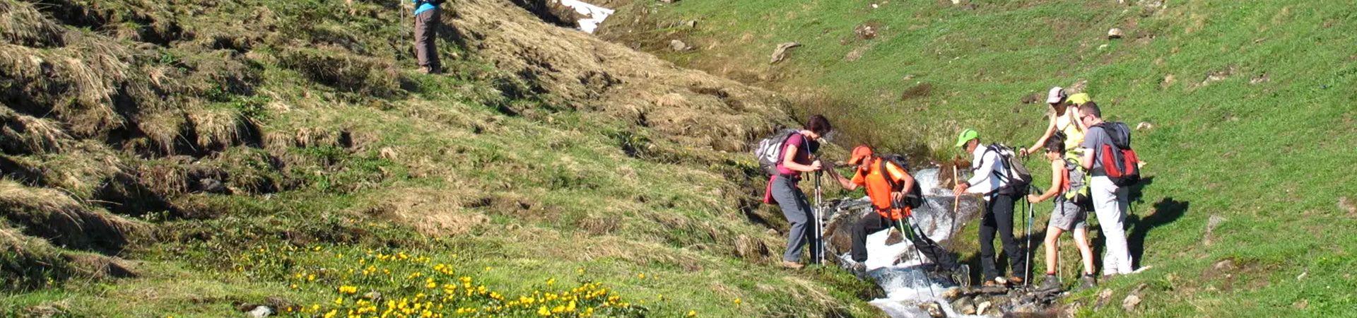 Randonneurs s'entraidant pour le franchissement d'un ruisseau en pleine montagne