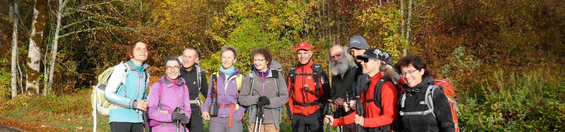 Randonneurs souriants avec des arbres aux couleurs d'automne en arrière-plan