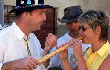 Une randonneuse essaie de jouer du cor des Alpes